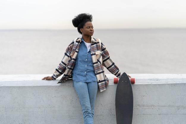 Garota africana em pé sobre a vista do rio, olhar de lado segurar longboard e usar roupas e acessórios urbanos da moda