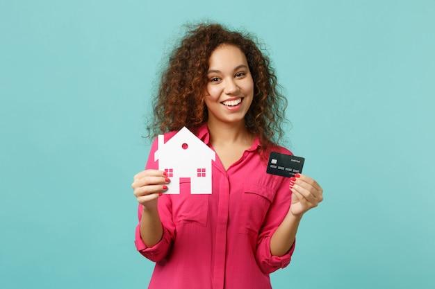 Garota africana engraçada com roupas rosa casuais segurando a casa de papel, cartão de crédito isolado no fundo da parede azul turquesa no estúdio. emoções sinceras de pessoas, conceito de estilo de vida. simule o espaço da cópia.