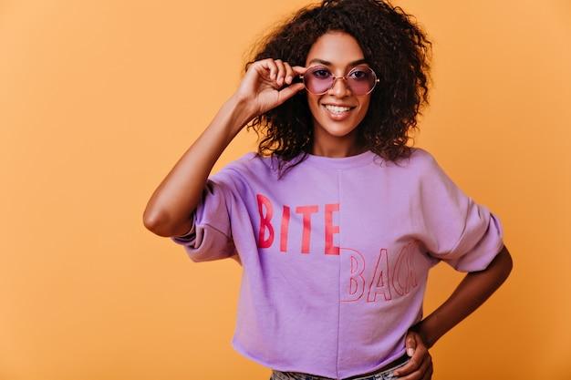 Garota africana entusiasmada tocando seus óculos de sol roxos e sorrindo. maravilhosa modelo feminino com cabelo preto em pé laranja.