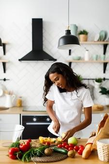 Garota africana está cortando um pimentão amarelo na mesa da cozinha e falando por telefone