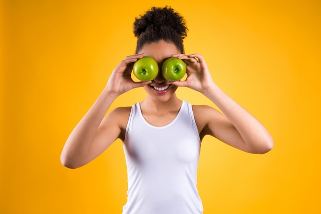 Garota africana fechou os olhos com maçãs