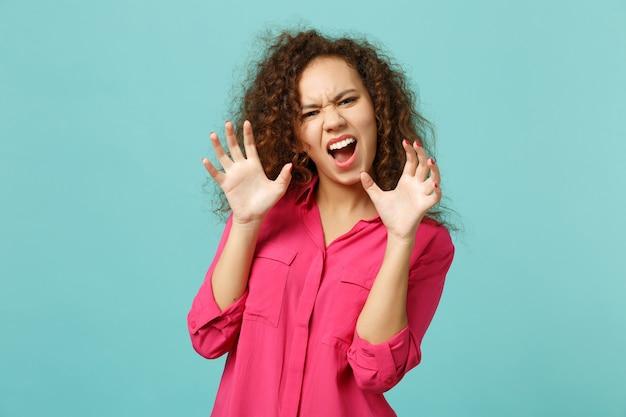 Garota africana louca em roupas casuais, gritando, rosnando como um animal, fazendo gesto de garras de gato isolado no fundo da parede azul turquesa. conceito de estilo de vida de emoções sinceras de pessoas. simule o espaço da cópia.