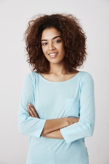 Garota africana na camisa azul sorrindo posando com braços cruzados.