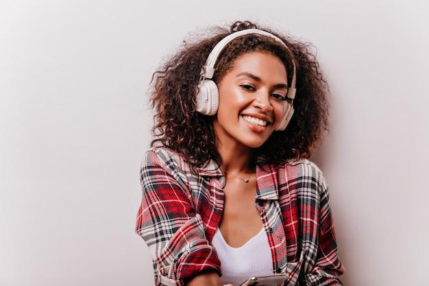 Garota africana relaxada com olhos grandes. mulher sorridente e atraente ouvindo música em branco