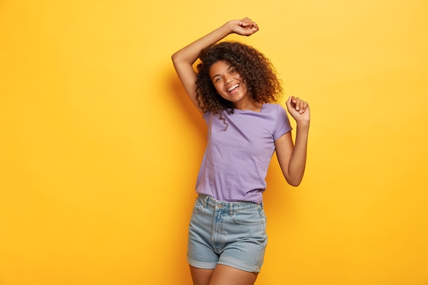 Garota afro-americana alegre e feliz levanta as mãos alegremente, em alto astral, dança ao som da música favorita, tem corpo esguio, vestida com roupas casuais