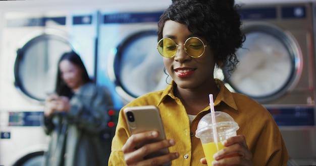 Garota afro-americana bebendo suco de laranja com palha, mensagem de texto no telefone e esperando a roupa ficar limpa mulher bebendo bebida na sala de serviço de lavanderia e tocando ou rolando no smartphone