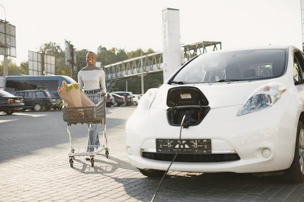 Garota afro-americana carregando carro elétrico no posto de gasolina elétrico