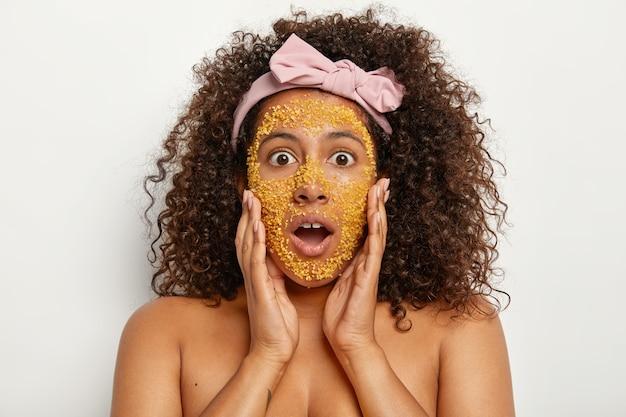 Garota afro-americana chocada aplica grânulos amarelos de máscara natural de sal para cuidados com a pele, mantém as mãos nas bochechas, usa uma faixa de cabeça em arco, ouve cosmetologista, surpresa com todos os benefícios úteis do esfoliante