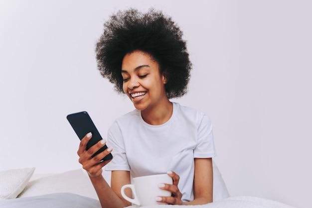 Garota afro-americana descansando na cama em casa mulher bonita relaxando em casa tomando café da manhã na cama w