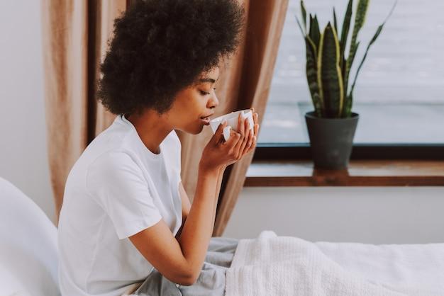 Garota afro-americana descansando na cama em casa mulher bonita relaxando em casa tomando café da manhã na cama