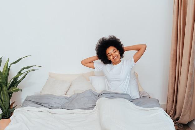 Garota afro-americana descansando na cama em casa - mulher bonita relaxando em casa