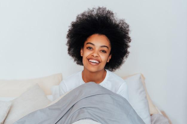 Garota afro-americana descansando na cama em casa mulher bonita relaxando em casa