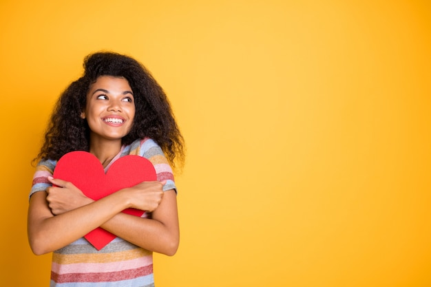 Garota afro-americana em camiseta listrada abraça cartão de coração vermelho do dia dos namorados