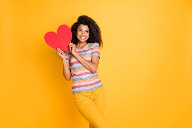 Garota afro-americana em camiseta listrada segurando um coração de cartão do dia dos namorados
