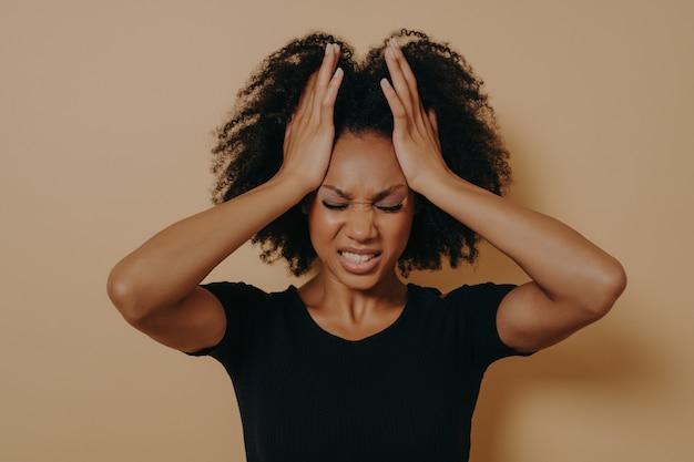 Garota afro-americana em pânico em choque, vestida com uma camiseta preta de mãos dadas na cabeça e gritando em desespero e frustração, com os olhos fechados e os dentes cerrados de raiva, posando no fundo do estúdio