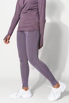 Garota afro-americana em retrato de estúdio de calças de ioga roxas