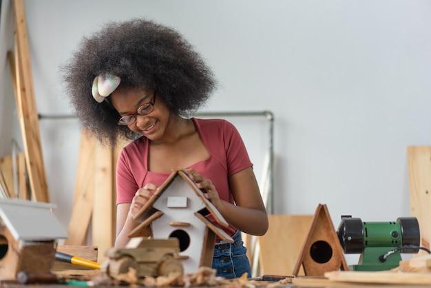 Garota afro-americana fazendo casinha de pássaros de madeira na oficina