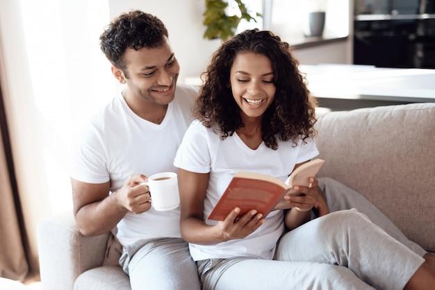 Garota afro-americana lê um livro com o namorado