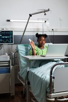 Garota afro-americana na enfermaria do hospital, usando tecnologia de videochamada no laptop. jovem doente sentado na cama com um dispositivo moderno para comunicação e conferência com conexão à internet