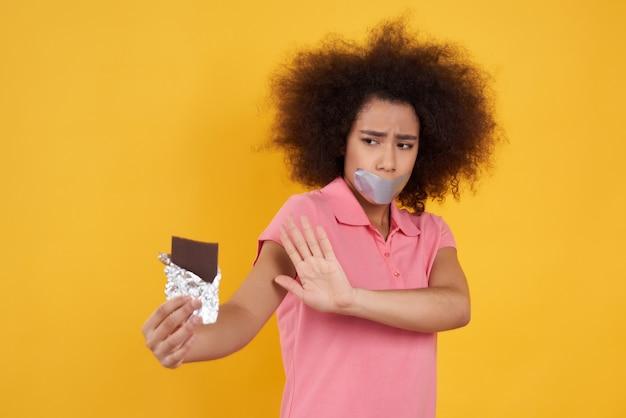 Garota afro-americana não pode comer chocolate isolado