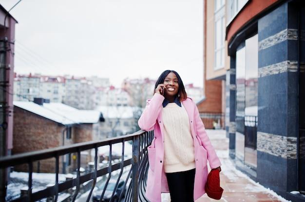 Garota afro-americana no chapéu vermelho e casaco rosa na rua da cidade contra a construção em dia de inverno com telefone móvel.