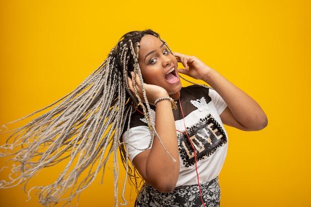Garota afro-americana, ouvindo música em um fone de ouvido amarelo