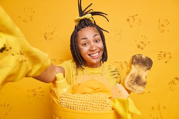 Garota afro-americana positiva com sorriso cheio de dentes cara suja estende o braço faz foto de si mesma enquanto lava a roupa em casa limpa a sujeira faz limpeza de primavera nos fins de semana isolada na parede amarela