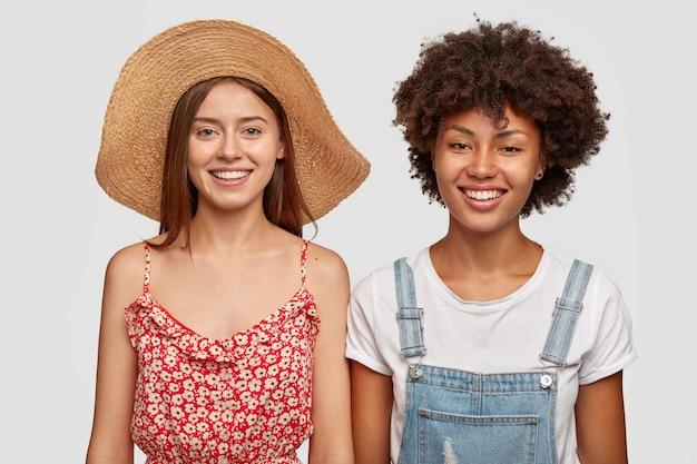 Garota afro-americana positiva tem sorriso dentuço, dentes brancos, usa macacão