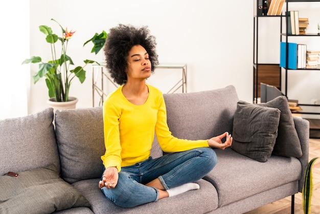 Garota afro-americana relaxando em casa com meditação de ioga