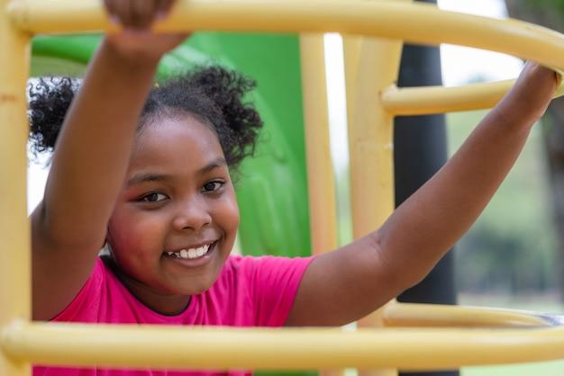 Garota afro-americana, sorrindo, olhar para a câmera enquanto se exercita no playground no parque