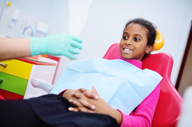 Garota afro-americana, sorrindo, sentado em uma cadeira odontológica