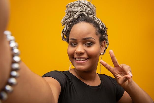 Garota afro-americana, tirando fotos de selfie com o celular em amarelo