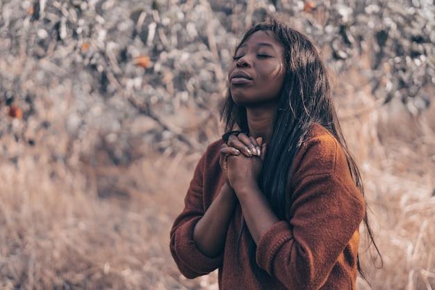 Garota afro de olhos fechados, orando ao ar livre