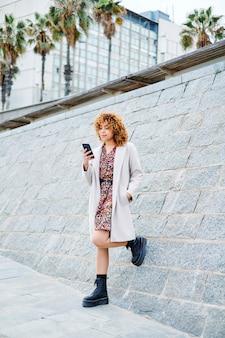 Garota afro encaracolada falando ao telefone na rua
