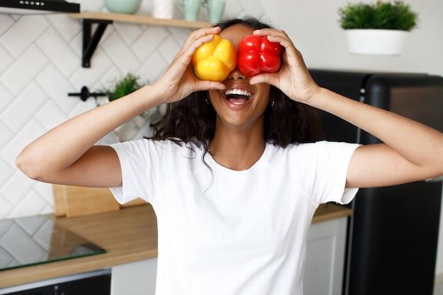 Garota afro joying detém duas pimentas