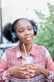 Garota afro negra em vestido étnico com fones de ouvido, sentado no café ao ar livre, ouvindo música e bebendo coquetel de leite