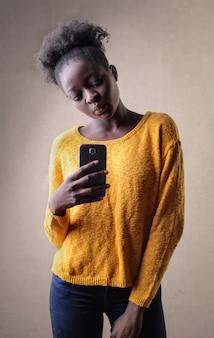 Garota afro, tirando uma foto com seu smartphone
