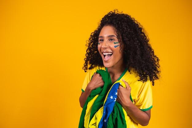Garota afro torcendo pelo time brasileiro favorito, segurando a bandeira nacional em fundo amarelo.