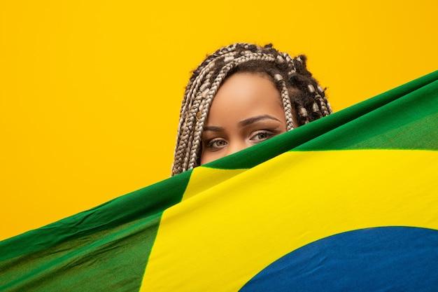 Garota afro torcendo por time brasileiro favorito, segurando a bandeira nacional em amarelo.