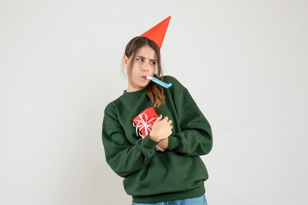 Garota agitada de frente com chapéu de festa escondendo seu presente de natal usando o fabricante de barulho