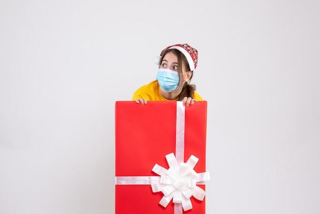 Garota agitada de frente com chapéu de papai noel atrás de um grande presente de natal