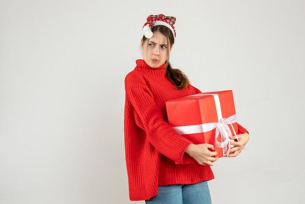 Garota agitada de frente com chapéu de papai noel escondendo seu presente