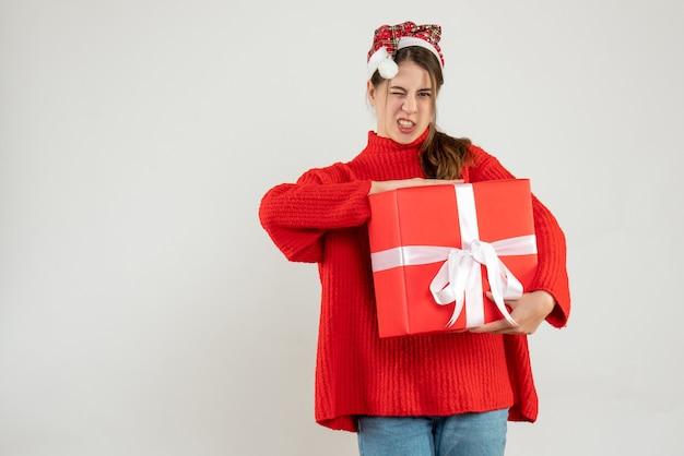 Garota agitada de frente com chapéu de papai noel segurando um presente