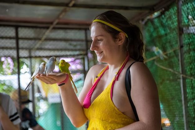 Garota alegre alimenta os papagaios de suas mãos e ri. entre em contato com o zoológico.
