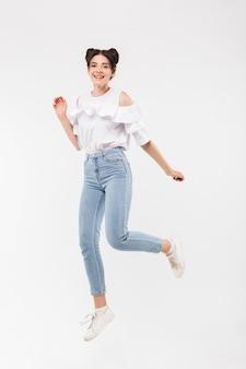 Garota alegre com penteado de dois pãezinhos sorrindo para você e correndo, isolado no branco