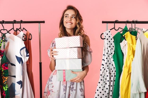 Garota alegre com um vestido em pé na loja perto do cabideiro com caixas de presentes isoladas em rosa