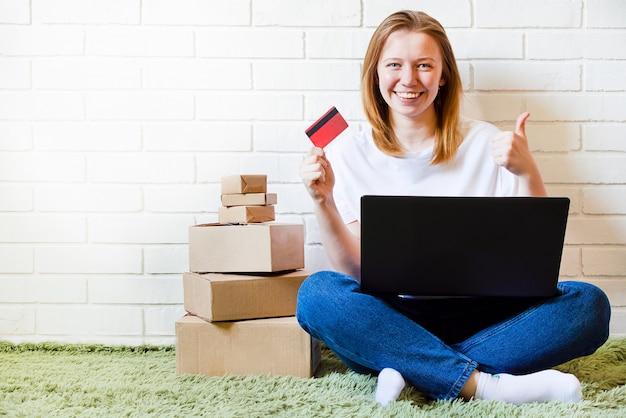 Garota alegre compra on-line no computador com cartão de crédito. entrega de encomendas online de compras.