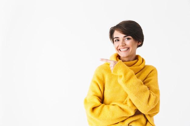 Garota alegre e feliz usando um capuz em pé isolado no branco, apontando o dedo para o espaço da cópia