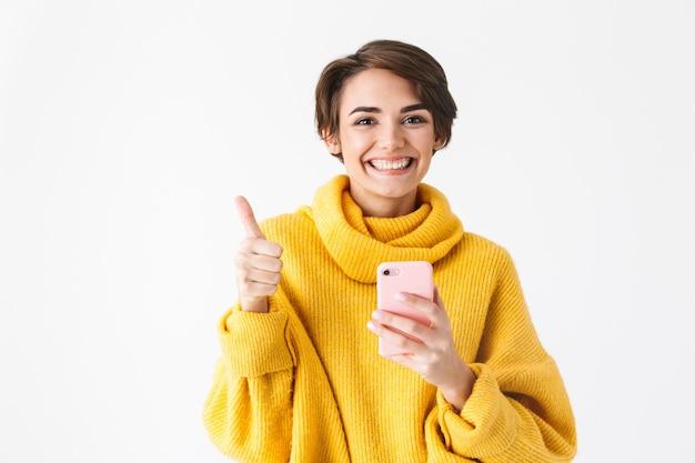 Garota alegre e feliz usando um capuz em pé, isolado no branco, segurando um telefone celular