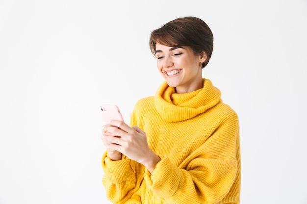 Garota alegre e feliz usando um capuz em pé, isolado no branco, usando um telefone celular